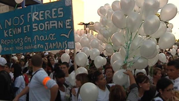 Des personnes participant mardi 2/10 à une marche blanche à la mémoire de Kevin et Sofiane, tués à la Villeneuve, à Echirolles, dans la banlieue de Grenoble.
