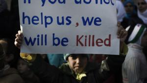 Un jeune manifestant brandissant un appel à la communauté internationale lors d'un défilé anti-régime à al-Qsair (3 février 2012)