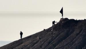 Syrie : combattants de l'Etat islamique plantant leur drapeau sur une colline près de Kobané, à la frontière avec la Turquie, 7/10/14