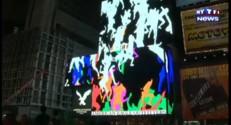 Un artiste diffuse des images de personnes rampant sur Times Square