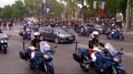 François Hollande, à bord de la DS5 gris métallisé, salue la foule sous un ciel gris anthracite