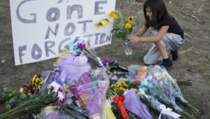 """Une fillette près de bouquets de fleurs en guise d'hommage aux victimes de la fusillade d'Aurora, dans un cinéma, lors de la première de """"Batman"""" (20 juillet 2012)"""