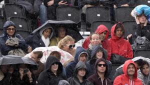 JO 2012 : spectateurs assistant sous la pluie à un match de phase préliminaire de beach volley (29 juillet 2012)