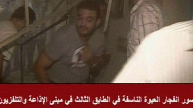 Un homme au milieu des débris laissés par l'explosion qui a touché le siège de la télévision syrienne à Damas, le 6 août 2012 (image de la TV syrienne).