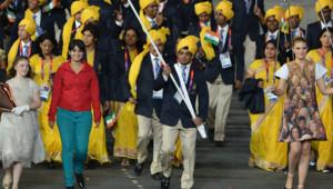 JO 2012 : une jeune femme à la chemise rouge vif et au pantalon bleu vert défile lors de la cérémonie d'ouverture aux côtés de l'équipe indienne (27/07/2012)