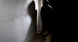 Un homme se tient dans une rue sombre, capuche sur la tête