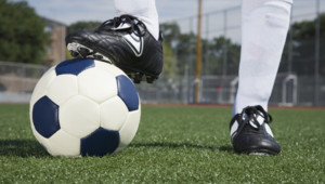 Soccer player's foot standing on ball