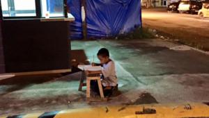 Daniel, 9 ans, faisant ses devoirs à la lumière d'un McDonald's