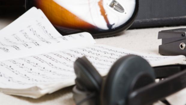 Une partition, une guitare et des écouteurs.