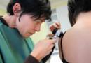 Une dermatologue observe un grain de beauté sur le dos d'une patiente (image d'illustration)