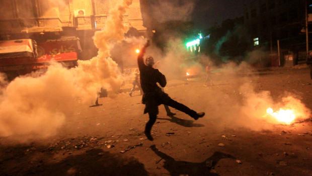 Manifestant égyptien renvoyant une grenade lacrymogène tirée par la police du Caire (4 février 2012)