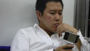 Un Japonais regarde la télévision sur son téléphone portable dans le métro tokyoïte