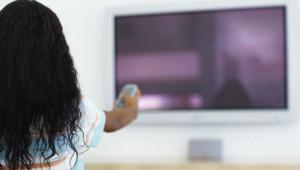 Une jeune femme allumant une télévision.