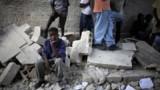 Jeunes garçon haïtien assis sur les ruines d'une école de Port-au-Prince (13 janvier 2010)
