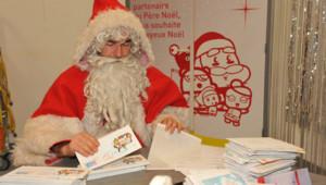 Père Noël ouvrant les lettres avant la distribution des cadeaux
