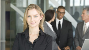 Portrait of young businesswoman, colleagues in background