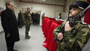 Gérard Longuet face aux cercueils de quatre soldats français tués en Afghanistan, lors d'une cérémonie à l'aéroport de Kaboul (21/01/2012)