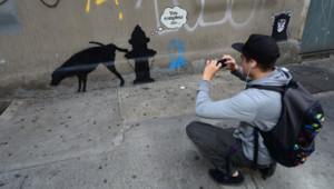 Un passant photographie un graffiti de Bansky peint sur un mur à New York.