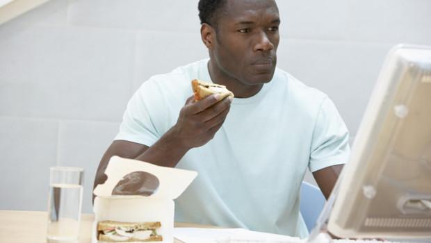 Un homme mange son sandwich devant son ordinateur.