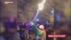 Le sportif russe Piotr Makartchouk porte la flamme avant que sa manche gauche prenne feu.