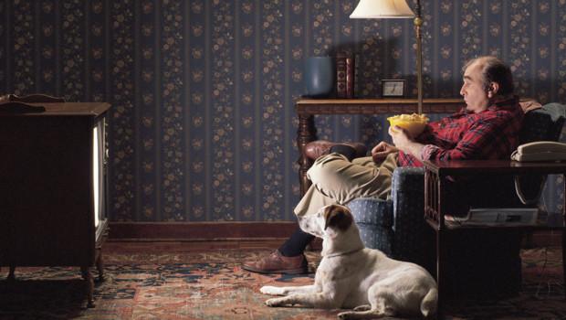 Un homme seul avec son chien devant devant la télévision.