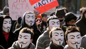 Des manifestants, le visage caché par le masque des Anonymous, défilent à Paris le 11 février 2012 contre l'accord européen ACTA.