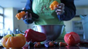 Karyne prépare des poivrons bios dans la cuisine d'Alain Berne, chef drômois locavore et utilisateur de produits biologiques.