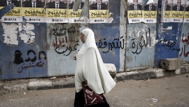 Egypte : femme du Caire devant des panneaux lectoraux pour la campagne prsidentielle, 30/4/12