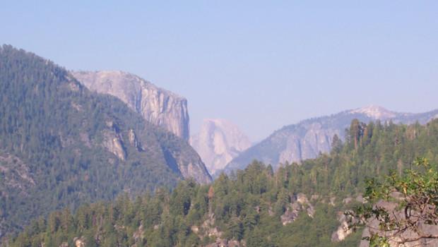 Vue de l'intérieur du parc Yosemite ; au fond à gauche, le mont Half Dome (juillet 2008)