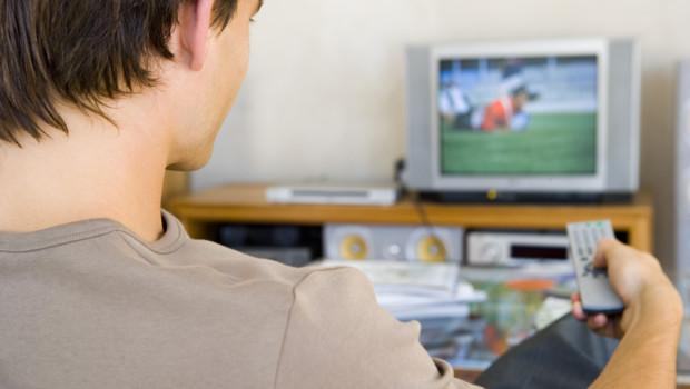 Un homme regarde la télévision.