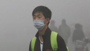 Un homme portant un masque filtrant à Harbin, en Chine, en raison d'un épais brouillard de pollution.