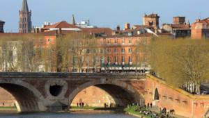 Vue de Toulouse depuis la Garonne. On aperçoit le Pont-Neuf et l'église Saint-Sernin en arrière plan.