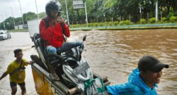 Un homme à moto regarde son téléphone alors que l'Indonésie est frappée par des inondations (février 2015)