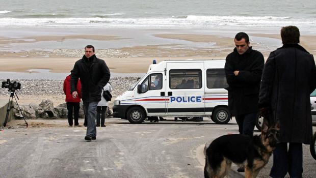 Des policiers sur une plage de Calais en 2005.