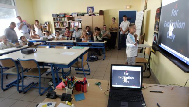Un écolier utilise un tableau blanc interactif lors d'une leçon de calcul.