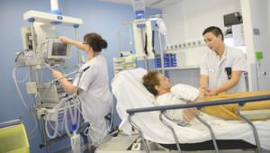 Pierre, infirmier, et Carole, aide-soignante entourent une patiente aux soins intensifs.