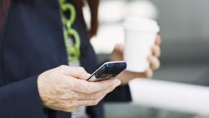 Une femme composant un numéro sur son téléphone portable.
