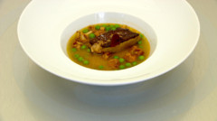 Foie gras pol au bouillon de homard, petits pois et girolles