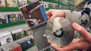 Un homme montre un compact disc dans un magasin