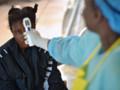 Un médecin prend la température d'une jeune fille suspectée d'être infectée par le virus Ebola. Kenema, Sierra Leone, 16 août 2014.