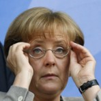 German Chancellor Merkel adjusts her eyeglasses before Euro 2008 semi-final between Turkey and Germany in Basel