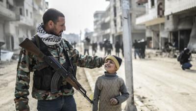 Un soldat kurde à Kobané avec son fils le 28 janvier 2015.