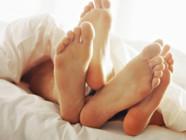 Zoom sur les pieds d'un couple dans un lit