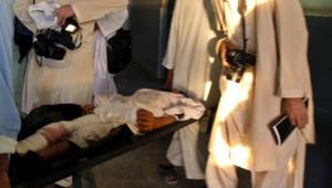 Stephen Farrel, journaliste irlandais du quotidien américain New York Times, et Sultan Munadi, son collègue afghan, interviewant un Afghan blessé