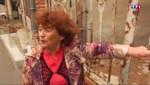 Une dame à la porte de sa maison squattée