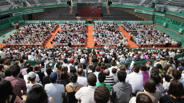 Spectateurs à Roland-Garros regardant sur un écran géant un match de tennis se déroulant sur le court n°1 (juin 2010)