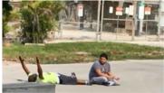 un Noir, allongé au sol les mains en l'air, se fait tirer dessus par la police de Miami