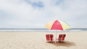 Des chaises longues sous un parasol à la plage