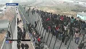 Images de migrants africains escaladant les barbelés d'une enclave espagnole