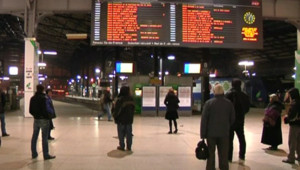 Usagers devant des panneaux d'affichage en gare (29 janvier 2009)
